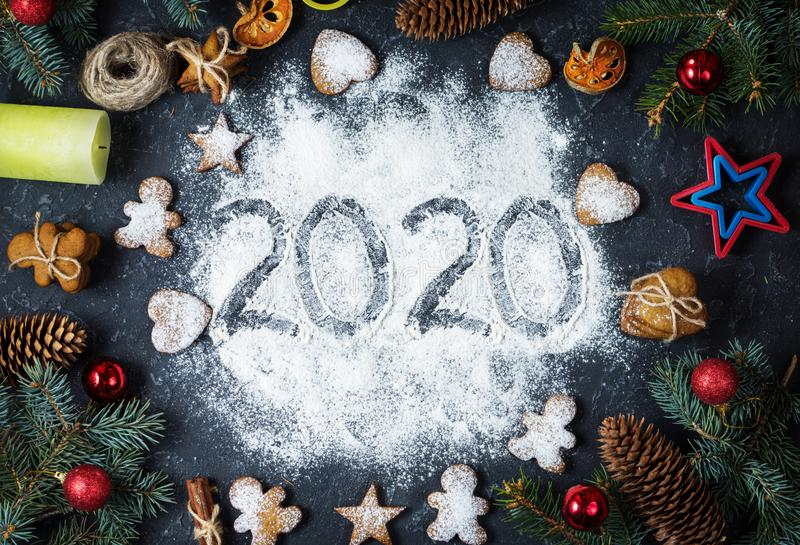 Happy New Year 2020 written on flour and Christmas Decorations Gingerbread cookies. New Year greeting card. Happy New Year 2020 written on flour and Christmas royalty free stock photography